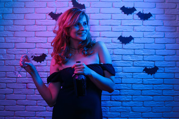 Happy gothic young woman with a bottle of wine and a glass partying in a nightclub, image with free space for design. Halloween, celebration, party concept