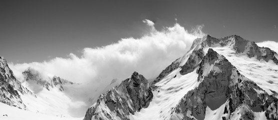 Black and white panoramic view on snow mountains