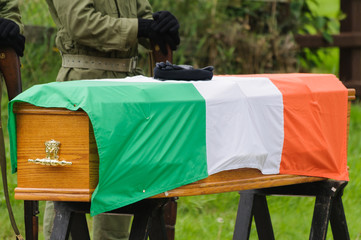 IRA paramilitary gloves and beret on a coffin with an Irish Tricolour flag. IRA man in background.