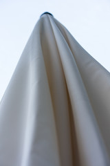closed parasol sun umbrella with clean background low angle view beige colour