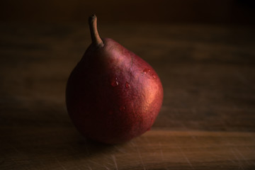 Red pear on wooden table top.