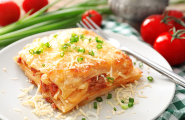 Plate with tasty lasagna on table