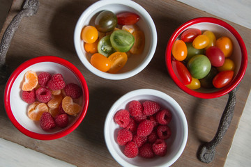 Snack idea, crackers, cheese, tomatoes, mandarin in enameled bowls