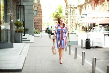Beautiful overweight woman in bright striped dress walking on city street