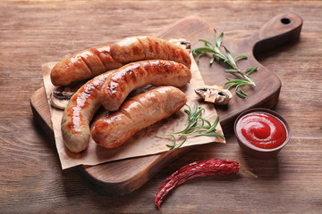 Wooden board with grilled sausages on table