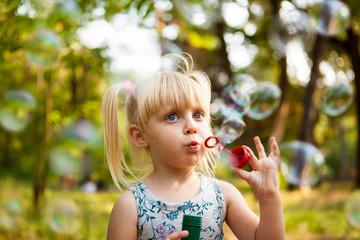 Cute little girl blows soap bubbles in park in summer