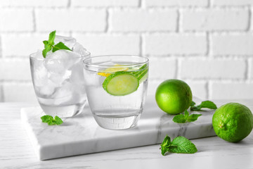Delicious refreshing water with cucumber in glass on board