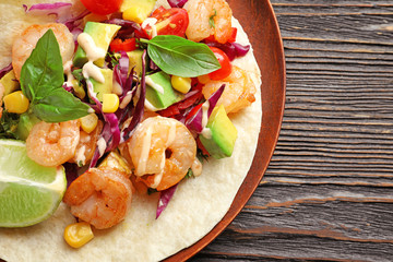 Plate with delicious shrimp taco on wooden table