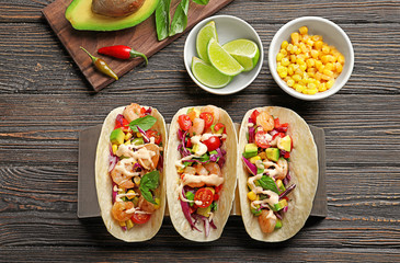 Holder with delicious shrimp tacos on wooden table