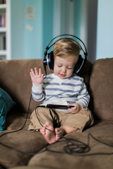 Cute young boy listening to music with big headphones