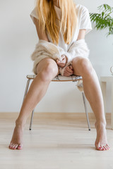 Unrecognizable sexy woman sitting on a white chair