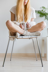 Young blonde woman sitting in a chair drinking tea