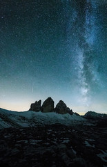 blue milky way above the famous three peaks in the italian alps in a clear night