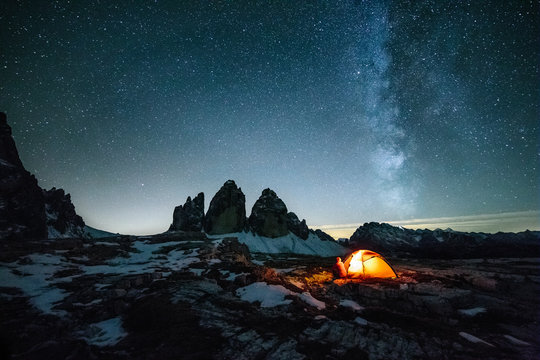 Man beside illuminated tent in front of peaks under milky way