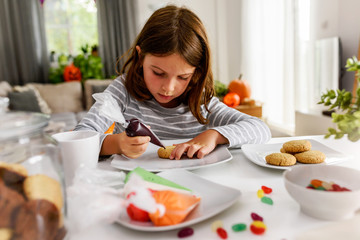 Young girl decorating cookies for Halloween
