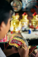 Local artist painting 'Hua Khon' traditional mask for Thai performing arts