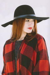 portrait of cool young woman with black hat on the white background
