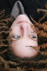 Beautiful blue eyed woman lying among autumn ferns