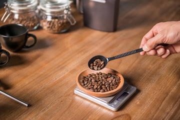 Man weighting coffee bean to prepare coffee