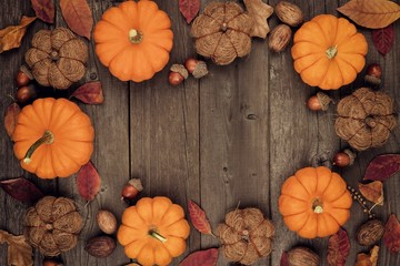 Autumn frame of pumpkins, leaves, nuts and rustic decor on an aged wood background