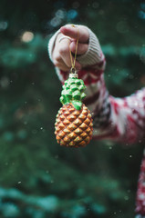 A young woman holding a Christmas ornament of a pineapple