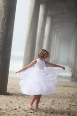 Girl in Formal White Dress Twirling On The Beach Under Pier