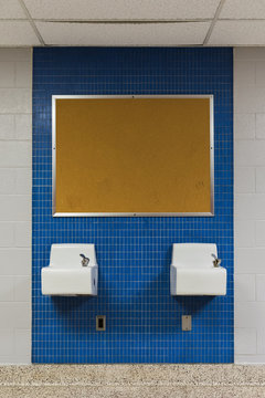 two drinking fountains and a bulletin board on blue tile