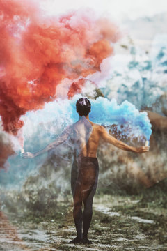 Ballet dancer with two colorful smoke bombs