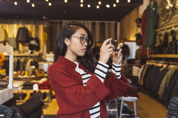 Stylish woman taking pictures with her phone in local downtown shop