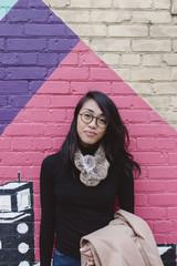 Stylish woman standing against urban street art