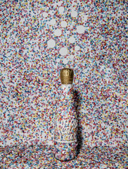 Bubbles above a champagne bottle with confetti everywhere