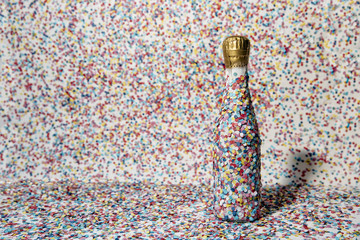 Champagne bottle covered with confetti