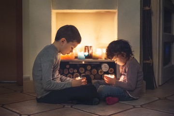 Siblings sitting in front of a fireplace holding candles in their hands and watching the flame
