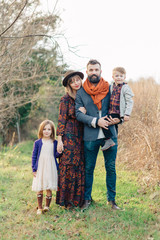 Beautiful and trendy family standing by a field