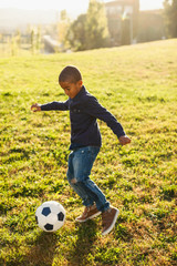 A 5 years old boy playing football in the park.