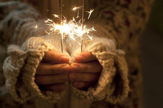 Close up shot of hands holding sparklers