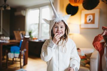 Girl in unicorn costume staring at camera