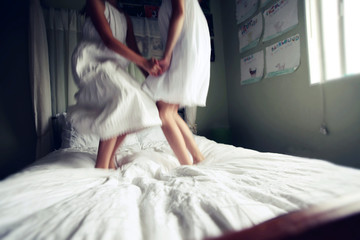 Two Girl in White Dresses Jumping on Bed