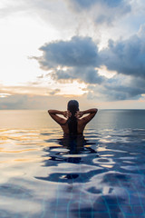 Woman at the edge of swimming pool with sea horizon and sky in background during sunset.