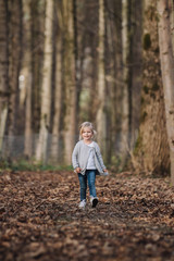 trendy cute little girl strolling through foliage covered forest