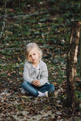 portrait of a sitting thoughtful looking cute little girl outdoors