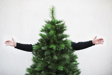 Happy man is hiding behind a Christmas tree
