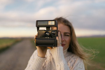 Woman taking photo with instant camera
