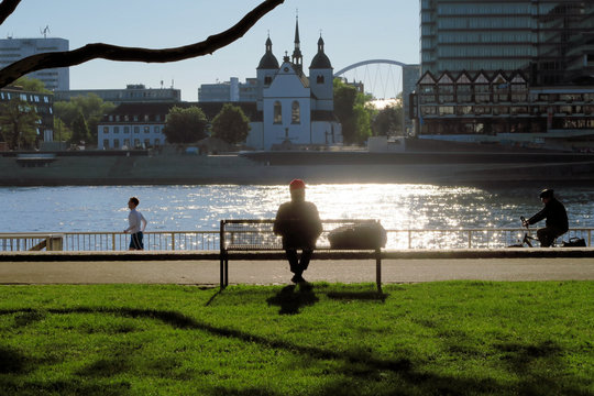 An old man in a red had sits on a bench in a German city alone the river as a jogger and a bicyclist pass by.
