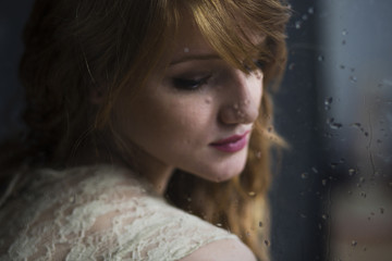 Portrait of a beautiful young woman and rainy window