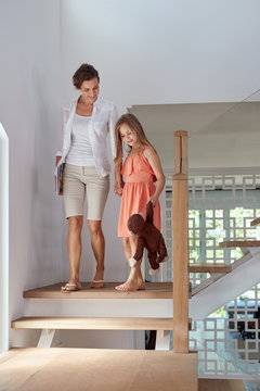 mother and daughter walking down stairs