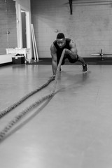 Fit and muscular african american athlete working out with exercise ropes