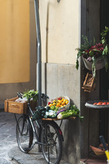 A bicycle parked outside a store loaded with veggies and fruits