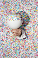 Surreal photo of a hand coming through a confetti wall, holding a balloon half covered with confetti