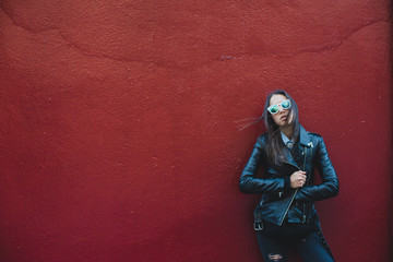 Girl in leather jacket against red wall